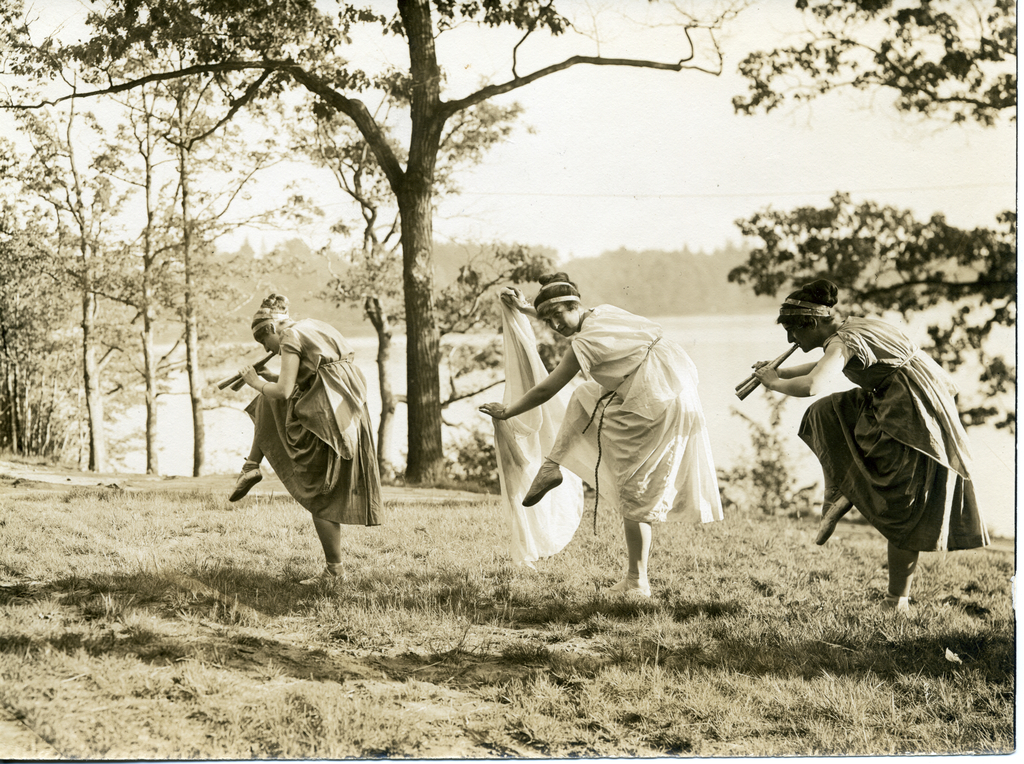 1912's Freshman Tree Day at Wellesley: three students dancing in Greek costume, including two with pipes