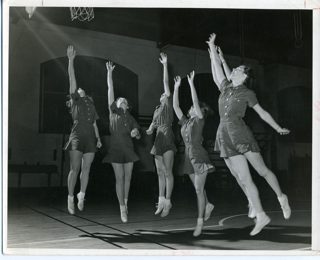 Basketball at Wellesley - six students leap toward the basket